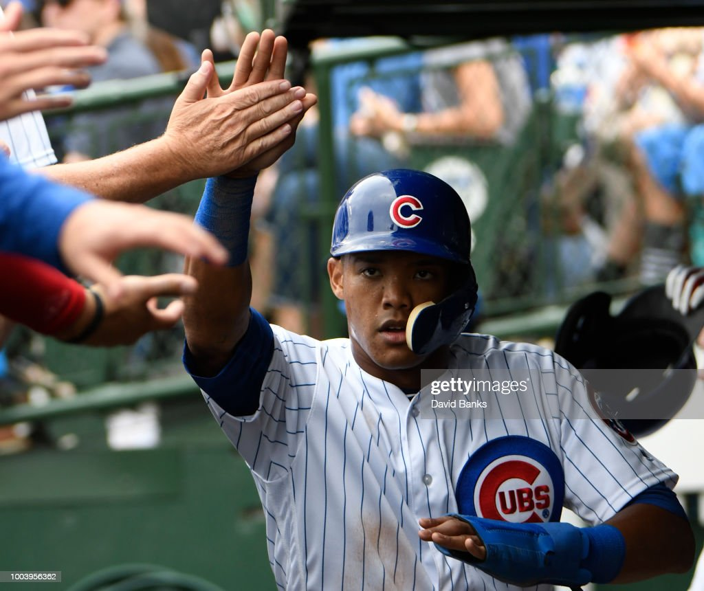 Addison Russell #27 of the Chicago Cubs is greeted after scoring against the St. Louis Cardinals during the seventh inning on July 22, 2018 at Wrigley Field in Chicago, Illinois.