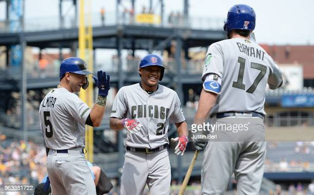 Addison Russell of the Chicago Cubs is greeted at home plate by Albert Almora Jr #5 and Kris Bryant after hitting a two run home run in the seventh...