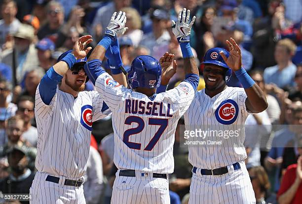 Addison Russell of the Chicago Cubs is greeted by Ben Zobrist and Jorge Soler after hitting a threerun home run in the 4th inning against the...
