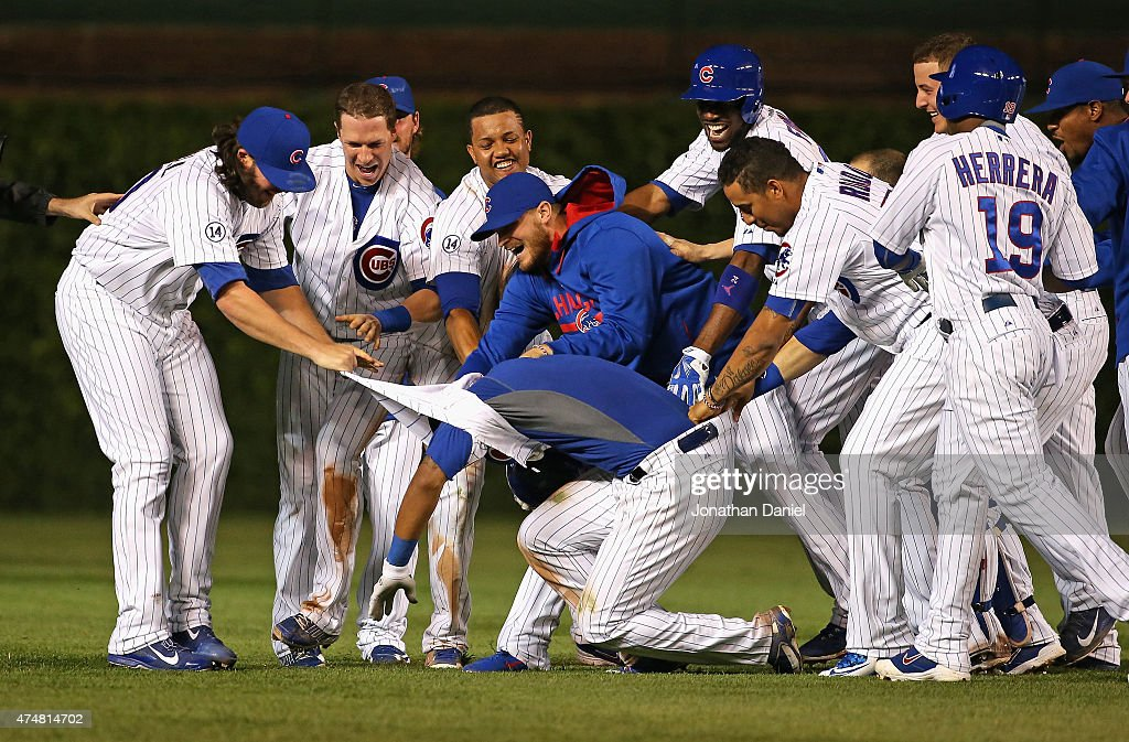 Addison Russell #22 of the Chicago Cubs (center, on ground) is mobbed by teammates after getting the game-winning hit, a double off of the center field wall, in the bottom of the 9th inning against the Washington Nationals at Wrigley Field on May 26, 2015 in Chicago, Illinois. The Cubs defeated the Nationals 3-2.