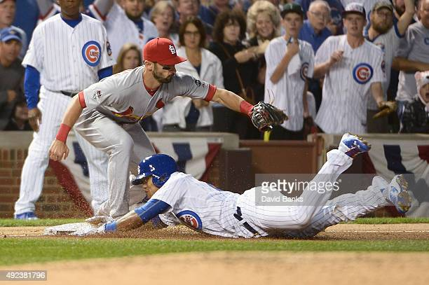 Addison Russell of the Chicago Cubs is safe at third base after hitting a triple as Matt Carpenter of the St Louis Cardinals covers in the fourth...