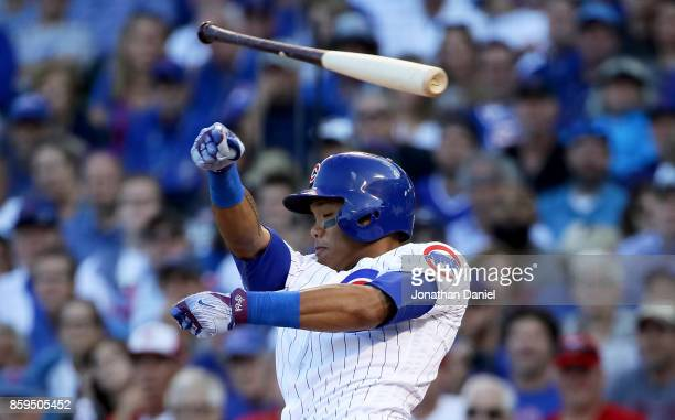 Addison Russell of the Chicago Cubs loses his bat during a swing in the fifth inning against the Washington Nationals during game three of the...