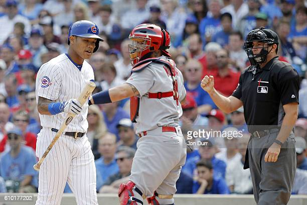 Addison Russell of the Chicago Cubs reacts after striking out against the St Louis Cardinals during the first inning at Wrigley Field on September 24...