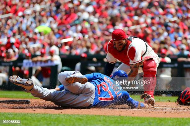 Addison Russell of the Chicago Cubs scores a run against Yadier Molina of the St Louis Cardinals in the second inning at Busch Stadium on May 5 2018...