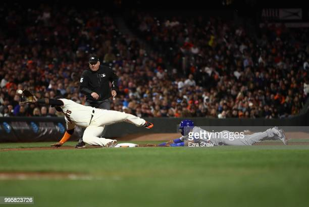Addison Russell of the Chicago Cubs slides safely in to third base as Pablo Sandoval of the San Francisco Giants dives for a wild throw from catcher...