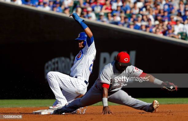 Addison Russell of the Chicago Cubs slides safely into second base as Dilson Herrera of the Cincinnati Reds stretches for the catch during the fourth...