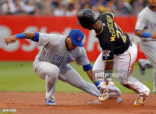Addison Russell of the Chicago Cubs tags out Andrew McCutchen of the Pittsburgh Pirates stealing in the first inning during the game at PNC Park on...