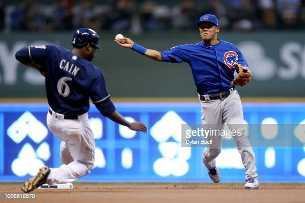Addison Russell of the Chicago Cubs turns a double play past Lorenzo Cain of the Milwaukee Brewers in the first inning at Miller Park on September 4...