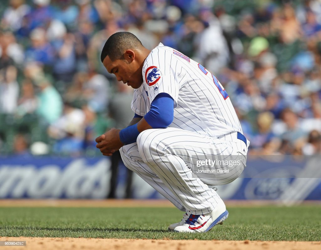 Addison Russell #27 of the Chicago Cubs waits as the grounds crew grooms the infield after striking out in the 7th inning against the Colorado Rockies at Wrigley Field on May 2, 2018 in Chicago, Illinois.