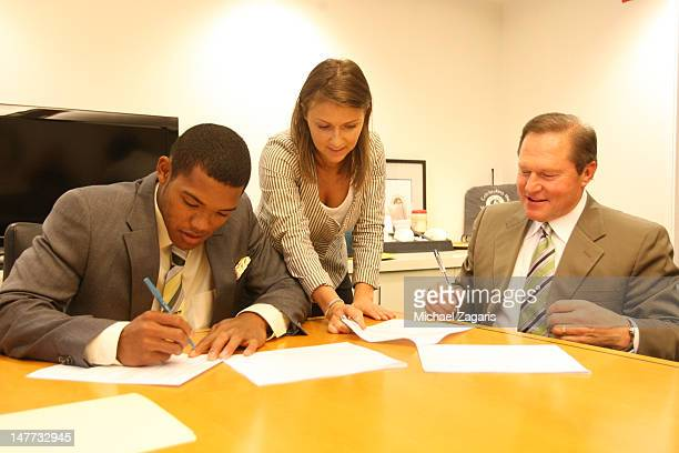 Addison Russell signs his contract with the Oakland Athletics as Athletics Scouting Assistant Kate Greenthal and Agent Scott Boris watch at the...