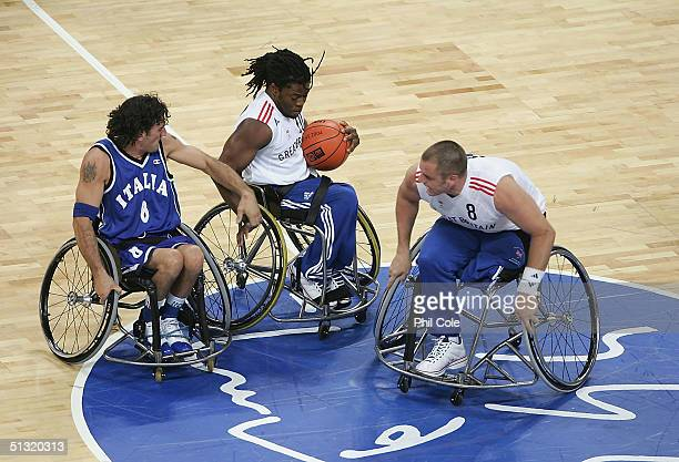 Ade Adepitan and Simon Munn of Great Britain against Fabio Raimondi of Italy during the Wheelchair Basketball match between Great Britain and Italy...