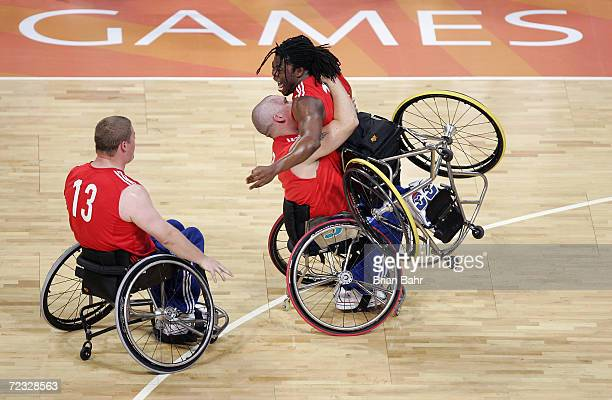Ade Adepitan of Great Britain exults in the arms of teammate Jon Pollock as Peter Finbow moves to join them after defeating the USA in wheelchair...