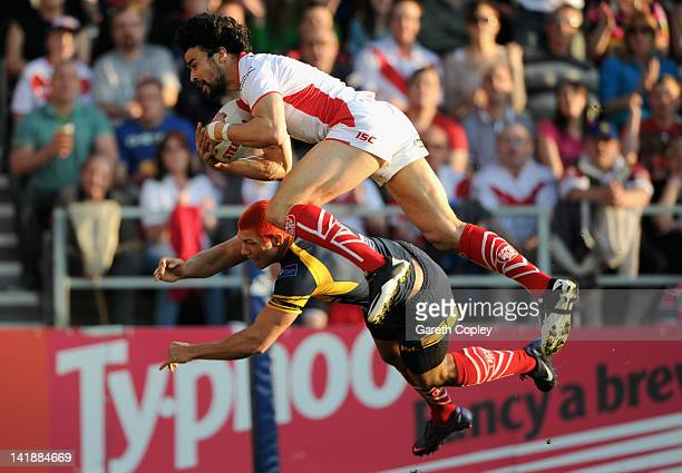 Ade Gardner of St Helens dives in past Ryan Hall of Leeds to score his team's opening try during the Stobart Super League match between St Helens and...