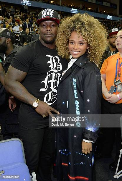 Adebayo Akinfenwa and Fleur East attend Orlando Magic vs Toronto Raptors NBA Global Game at The O2 Arena on January 14 2016 in London England