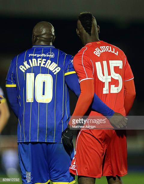 Adebayo Akinfenwa of AFC Wimbledon and Mario Balotelli of Liverpool