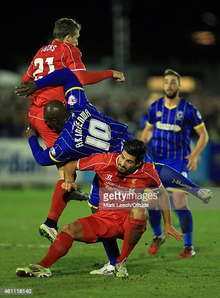Adebayo Akinfenwa of AFC Wimbledon collides with Lucas Leiva and Emre Can of Liverpool during the FA Cup Third Round match between AFC Wimbledon and...