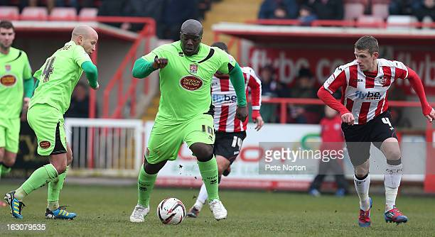 Adebayo Akinfenwa of Northampton Town looks to control the ball watched by Scot Bennett of Exeter City during the npower League Two match between...