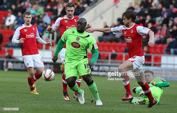 Adebayo Akinfenwa of Northampton Town moves with the ball between David Noble and Kari Arnason of Rotherham United during the npower League Two match...