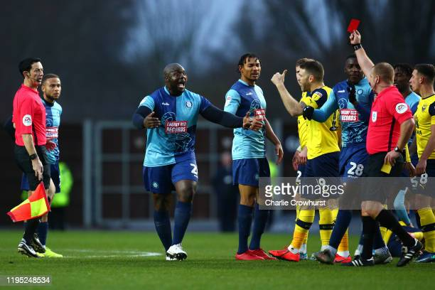 Adebayo Akinfenwa of Wycombe looks shocked as he is shows a red card after picking up a second yellow after pushing Oxford's John Mousinho during the...