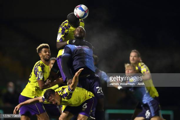 Adebayo Akinfenwa of Wycombe Wanderers battles for a header with Naby Sarr and Jonathan Hogg of Huddersfield Town during the Sky Bet Championship...