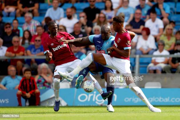 Adebayo Akinfenwa of Wycombe Wanderers battles for the ball with Reece Oxford and Pedro Obiang of West Ham during the preseason friendly match...