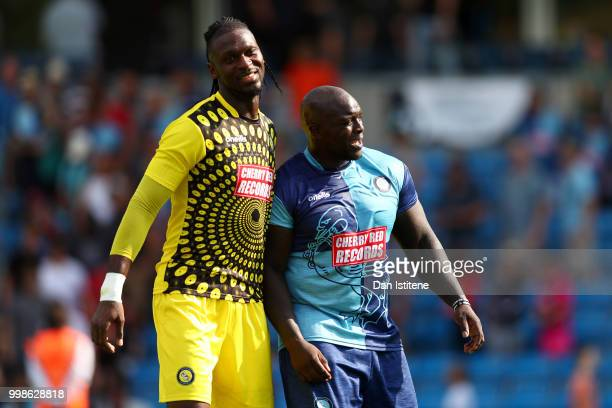 Adebayo Akinfenwa of Wycombe Wanderers embraces teammate Yves MaKalambay after the preseason friendly match between Wycombe Wanderers and West Ham...