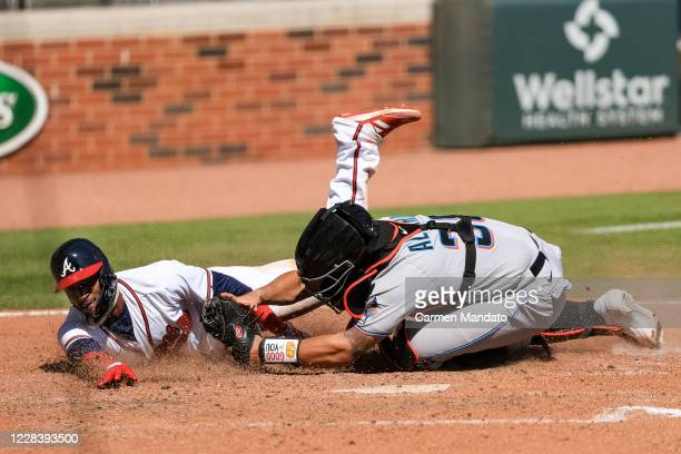 Adeiny Hechavarria of the Atlanta Braves is tagged out at home by Jorge Alfaro of the Miami Marlins in the seventh inning of a game at Truist Park on...