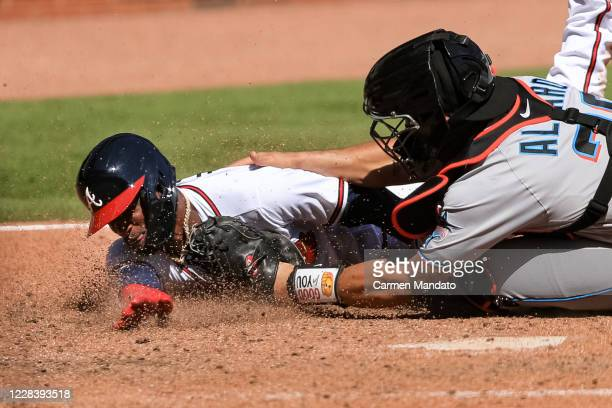 Adeiny Hechavarria of the Atlanta Braves is tagged out at home by Jorge Alfaro of the Miami Marlins in the seventh inning at Truist Park on September...