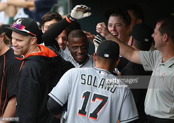 Adeiny Hechavarria of the Miami Marlins celebrates his game winning solo home run off of Boone Logan of the Colorado Rockies in the dugout in the...