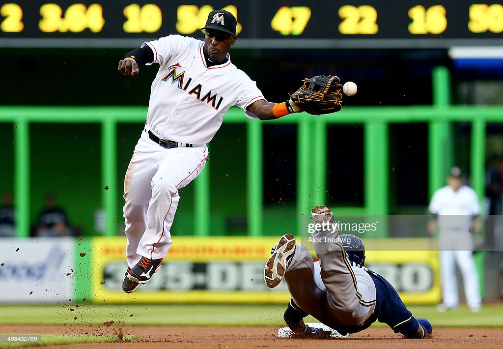 Adeiny Hechavarria #3 of the Miami Marlins fails to make the catch as Jean Segura #9 of the Milwaukee Brewers slides into second during a game at Marlins Park on May 23, 2014 in Miami, Florida.