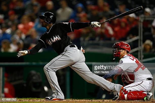 Adeiny Hechavarria of the Miami Marlins hits a single RBI in the second inning against the Washington Nationals at Nationals Park on September 30...