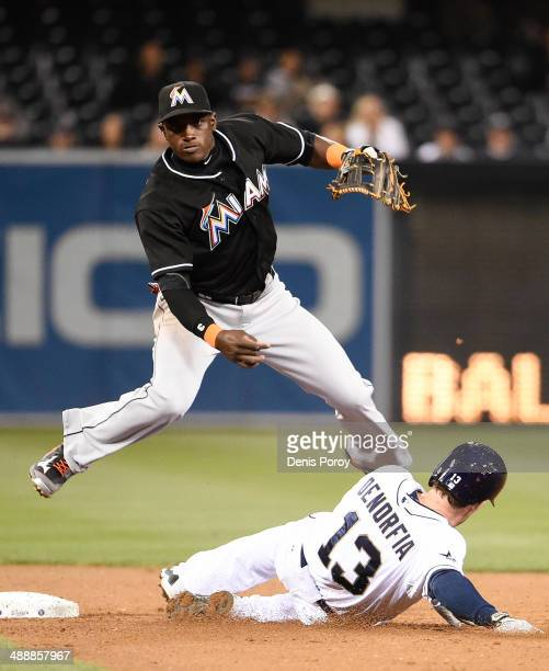 Adeiny Hechavarria of the Miami Marlins jumps over Chris Denorfia of the San Diego Padres as he turns a double play during the fifth inning of a...