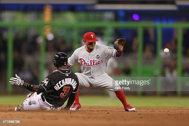 Adeiny Hechavarria of the Miami Marlins slides into second base ahead of the tag from Freddy Galvis of the Philadelphia Phillies during the game at...