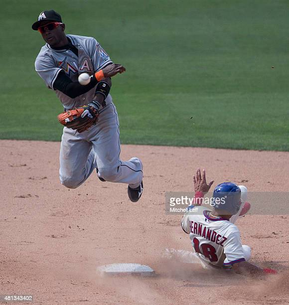 Adeiny Hechavarria of the Miami Marlins tunrs a double play as Cesar Hernandez of the Philadelphia Phillies slides into him in the bottom of the...