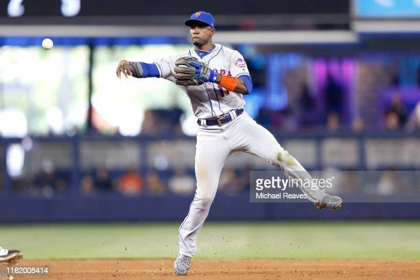 Adeiny Hechavarria of the New York Mets throws out a runner at first base against the Miami Marlins at Marlins Park on July 14 2019 in Miami Florida