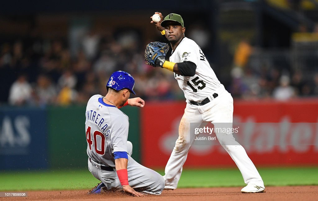 Adeiny Hechavarria #15 of the Pittsburgh Pirates attempts to turn a double play against Willson Contreras #40 of the Chicago Cubs in the seventh inning during the game at PNC Park on August 16, 2018 in Pittsburgh, Pennsylvania.