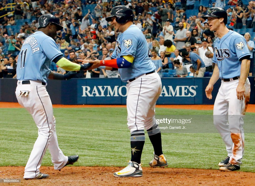 Adeiny Hechavarria #11 of the Tampa Bay Rays begins to celebrate after reaching home plate on a home run which brought in Jesus Sucre #45, center, and Joey Wendle #18 during the bottom of the sixth inning of the game against the Minnesota Twins at Tropicana Field on April 22, 2018 in St. Petersburg, Florida.