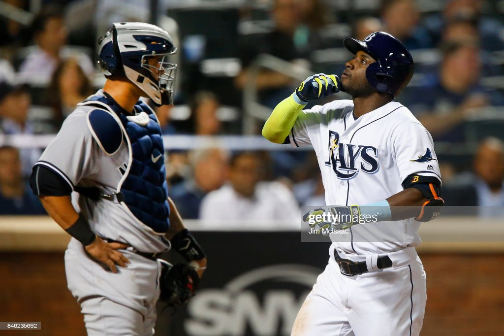 Adeiny Hechavarria #11 of the Tampa Bay Rays celebrates his eighth inning home run at home plate as Gary Sanchez #24 of the New York Yankees looks on at Citi Field on September 12, 2017 in the Flushing neighborhood of the Queens borough of New York City. The two teams were scheduled to play in St. Petersburg, Florida but due to the weather emergency caused by Hurricane Irma, the game was moved to New York, but with Tampa Bay remaining the 'home' team.