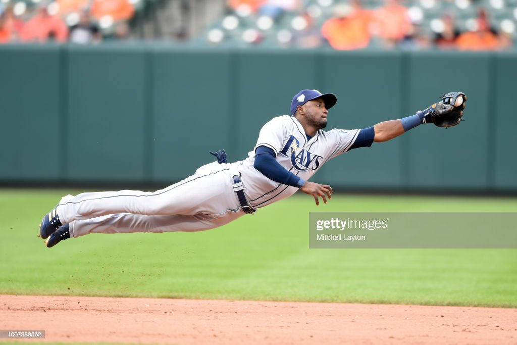 Adeiny Hechavarria #11 of the Tampa Bay Rays dives after a hit by Mark Trumbo #45 of the Baltimore Orioles in the eight inning during a baseball game at Oriole Park at Camden Yards on July 29, 2018 in Baltimore, Maryland.