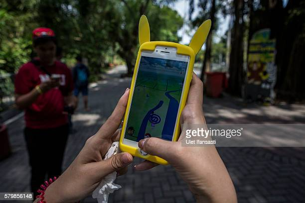 Adel plays Pokemon Go game on a smartphone at Gembira Loka Zoo on July 23 2016 in Yogyakarta Indonesia 'Pokemon Go' which uses Google Maps and a...