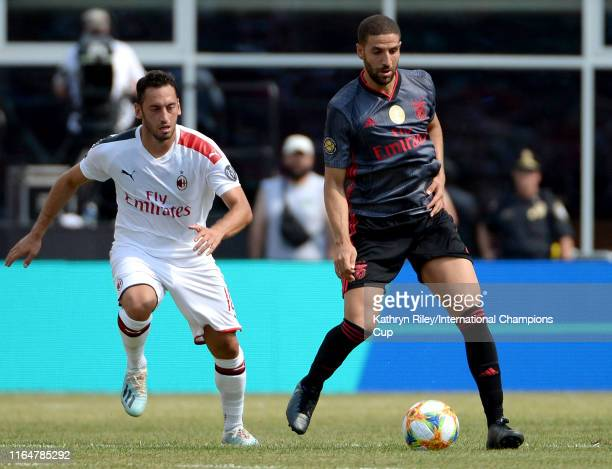 Adel Taarabt of Benfica is pursued by Hakan Calhanoglu of AC Milan during the International Champions Cup match at Gillette Stadium on July 28 2019...