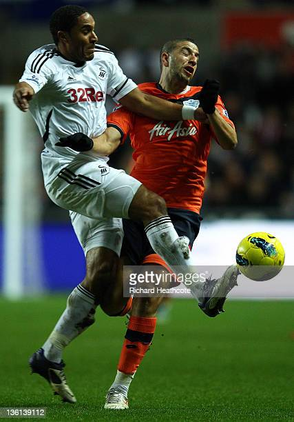 Adel Taarabt of QPR is tackled by Ashley Williams of Swansea during the Barclays Premier League match between Swansea City and Queens Park Rangers at...
