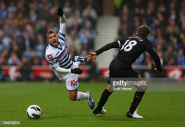Adel Taarabt of Queens Park Rangers is tripped by Phil Neville of Everton during the Barclays Premier League match between Queens Park Rangers and...