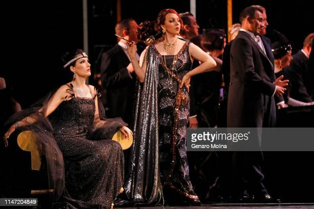 """Adela Zaharia, left, and Erica Petrocelli, center, perform in Los Angeles Opera's production of Verdi's """"La Traviata,"""" at the Dorothy Chandler..."""