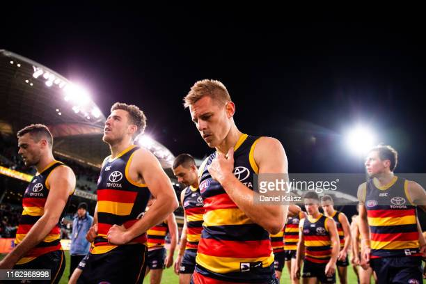 Adelaide Crows players walk from the ground looking dejected during the round 18 AFL match between the Adelaide Crows and the Essendon Bombers at...