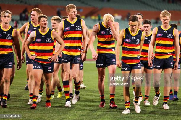 Adelaide Crows players walk from the ground looking dejected during the round 10 AFL match between the Adelaide Crows and the Melbourne Demons at...