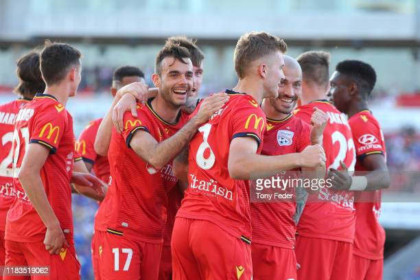 Adelaide players celebrate a goal by Riley McGree of Adelaide United during the round three A-League match between the Newcastle Jets and Adelaide...