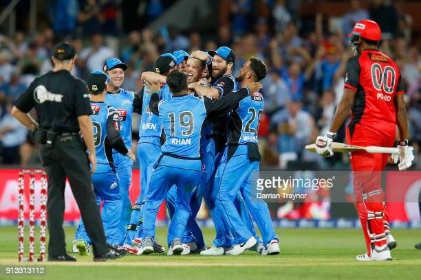 Adelaide Strikers players celebrate winning as a dejected Kieron Pollard of the Renegades look on after the Big Bash League match between the...