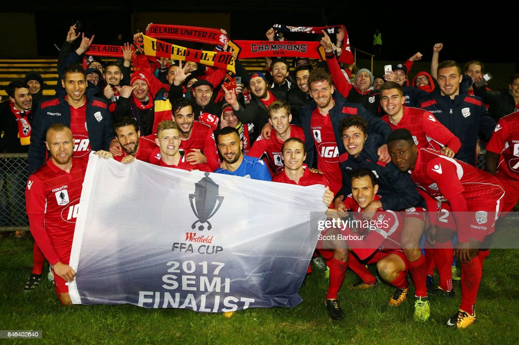 Adelaide United pose with the Westfield FFA Cup semi final qualification flag and their supporters in the crowd after winning the FFA Cup Quarter Final match between Heidelberg United FC and Adelaide United at Olympic Village on September 13, 2017 in Melbourne, Australia.