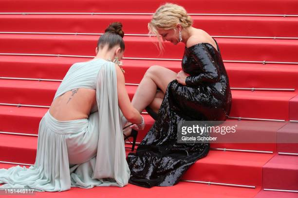 Adele Exarchopoulos ties Virginie Efira shoes before the screening of Sibyl during the 72nd annual Cannes Film Festival on May 24 2019 in Cannes...